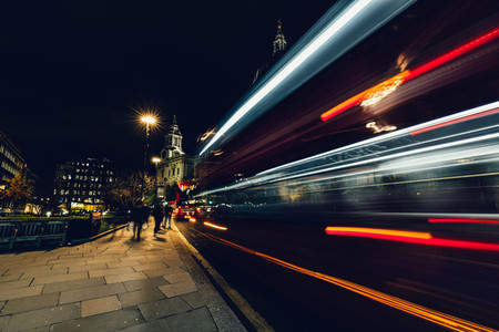 City light trails of moving red London bus at night