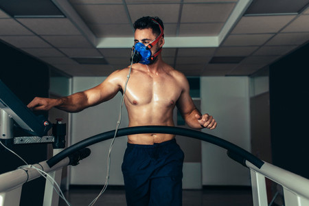 Professional athlete on treadmill monitoring his performance