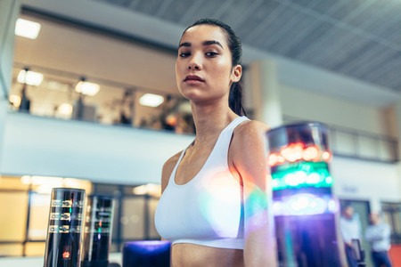 Sportswoman at gym with lights around