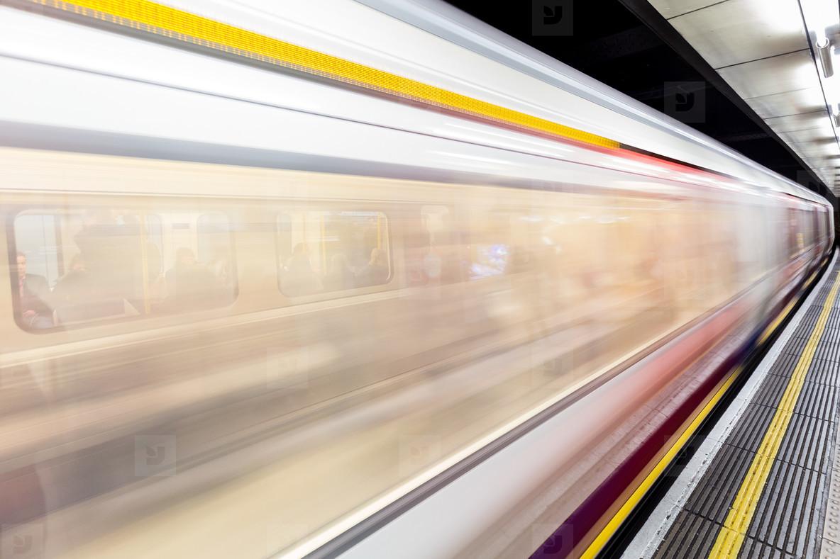 Motion blurred moving train on London Underground tube station