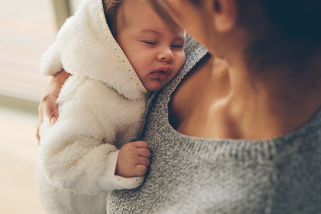 Cute little boy sleeping in his mother039 s arms