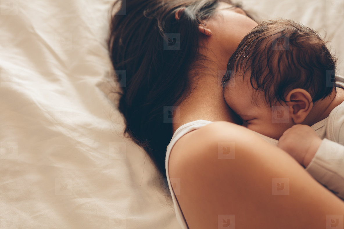 Newborn baby boy sleeping with his mother on bed