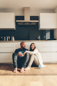 Couple sitting on kitchen floor and having coffee