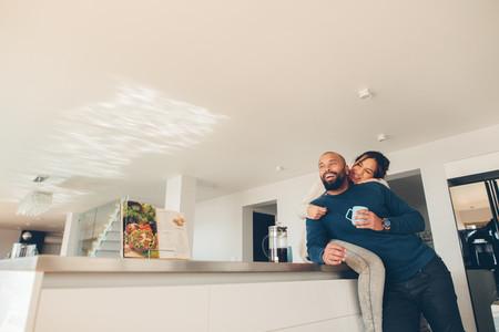 Loving couple enjoying morning coffee in kitchen