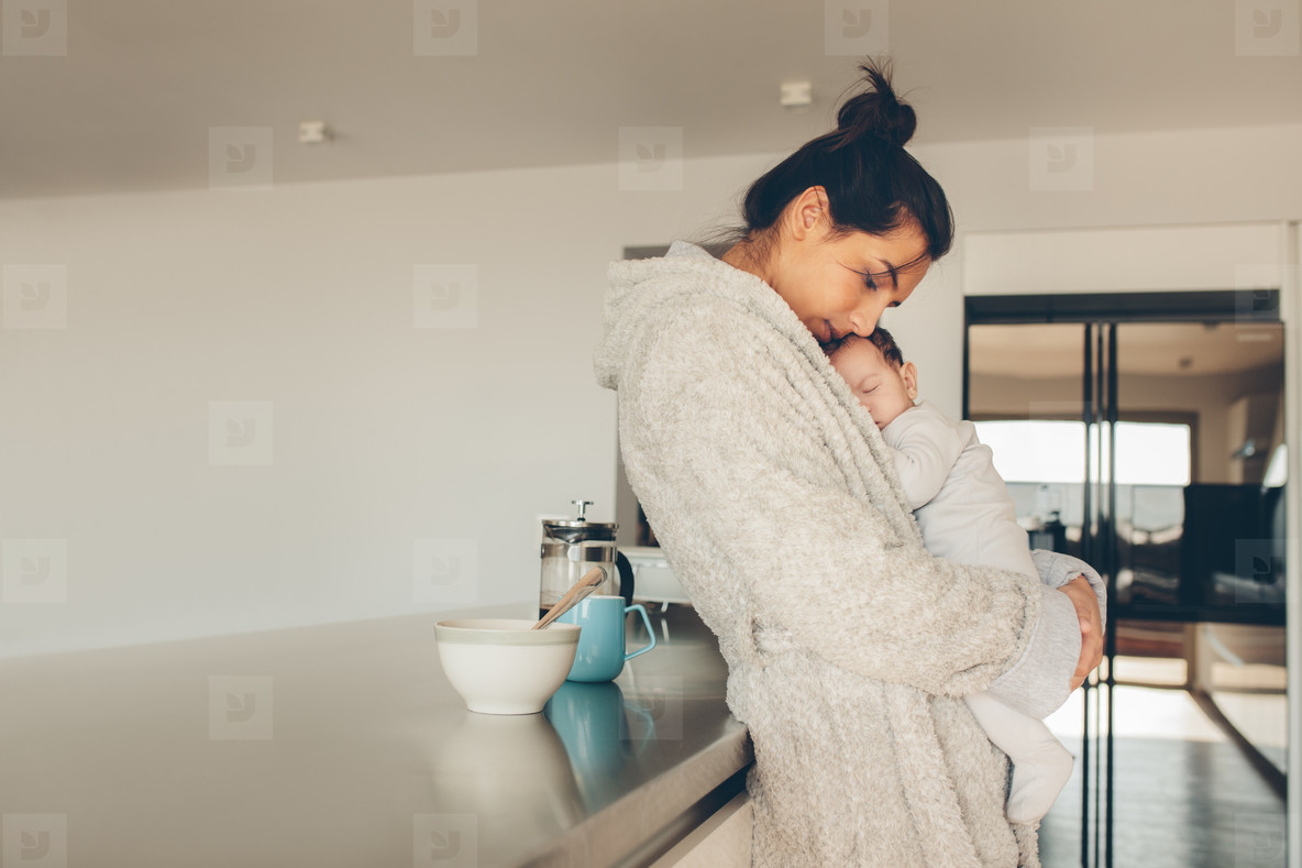 Woman in bathrobe with her son in kitchen