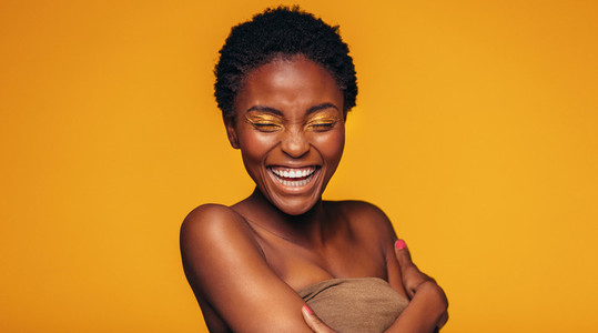 African woman laughing against yellow background