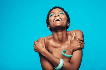 African woman with vivid makeup hugging herself