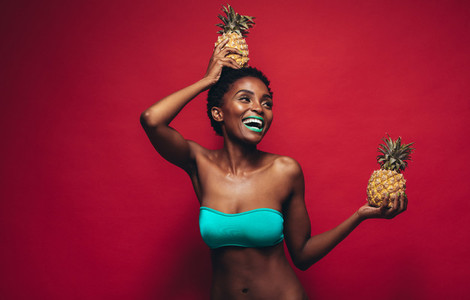 Beautiful young woman with pineapples