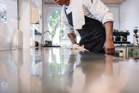 Waiter wiping the counter top in the kitchen