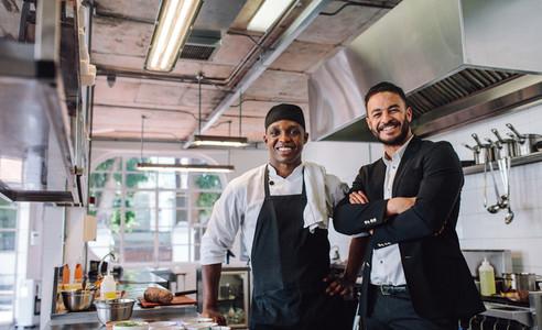 Restaurant owner with chef in kitchen