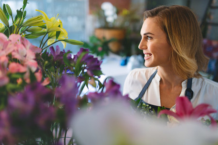 Smiling woman working at indoor plant nursery