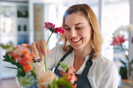 Female florist arranging flowers in bouquet