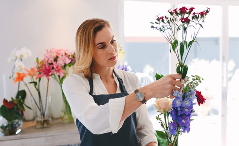 Female working at flower shop arranging flowers