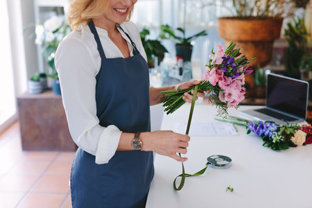 Female florist creating bouquet at shop