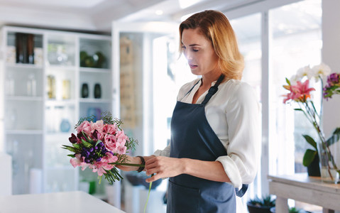 Woman florist arranging and designing bouquet