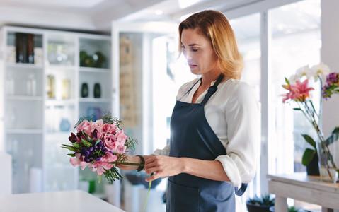 Woman florist arranging and designing bouquet