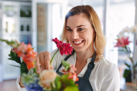 Smiling female florist preparing a bouquet