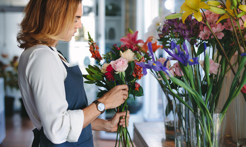 Florist preparing a bouquet with fresh flowers