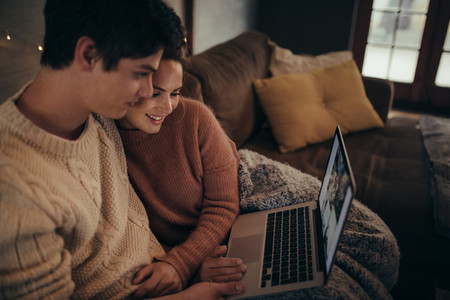 Couple using laptop in hygge house