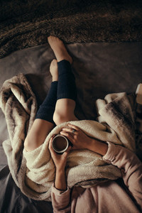 Woman lying on bed with a cup of coffee