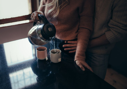 Romantic man and woman in kitchen making coffee