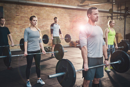 Strong man leading group in barbell exercises