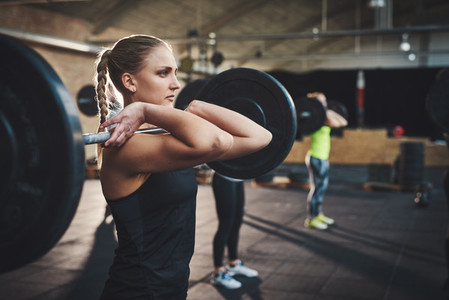 Woman pulling up large barbell in fitness class