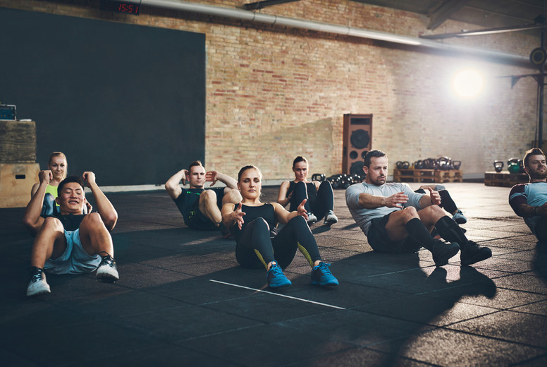 Athletic adults performing sit up exercises