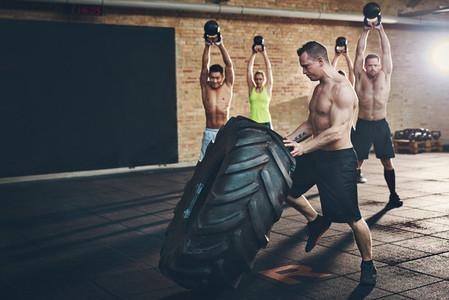 Muscular shirtless man moving large tire