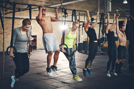 Adults doing chin ups for cross fit training