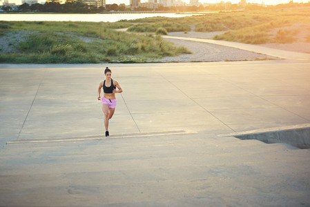 Athletic female long distance runner out jogging