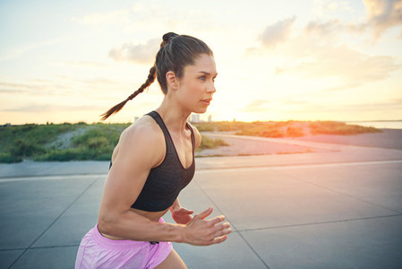 Young woman runner working out at sunrise
