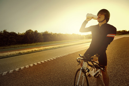 The cyclist drinking water on a bike