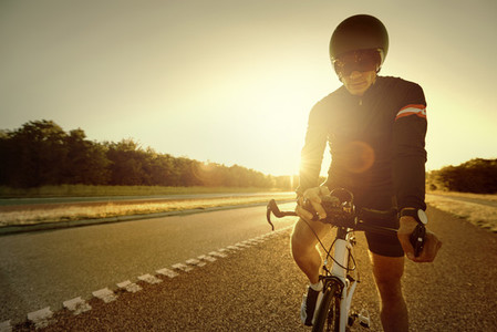 Sportsman standing and setting bicycle on road