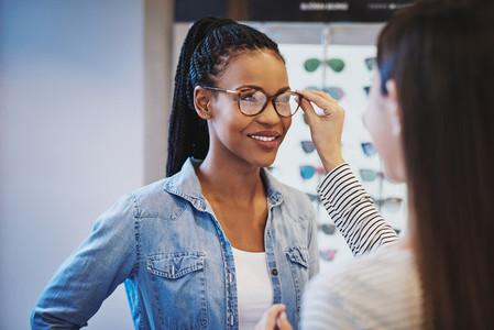Optometrist fitting glasses on a customer