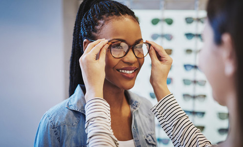 Attractive young African woman selecting glasses