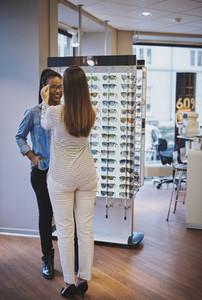 Optometrist fitting glasses for a customer