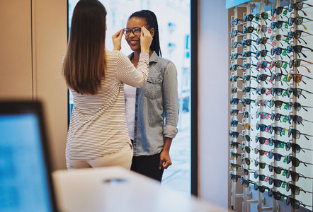 Optometrist helping a young woman in her store