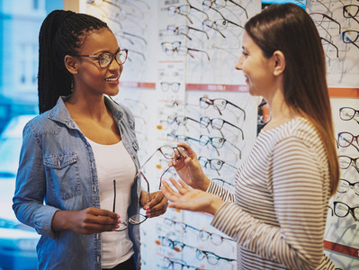 Pretty young woman chooses new glasses in store