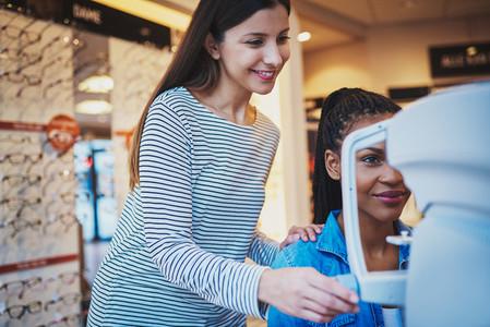 Pretty optometrist helps woman take her eye exam
