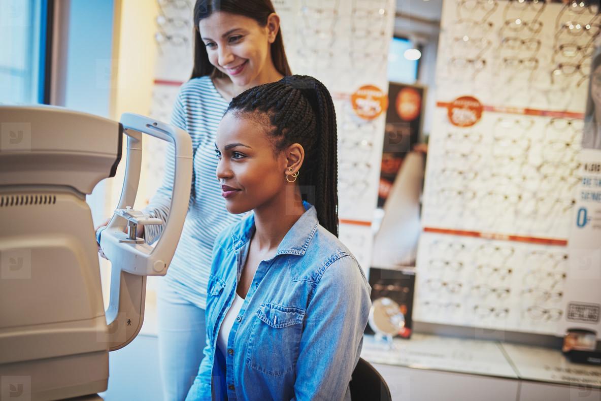 Serious black woman takes eye exam in optical shop