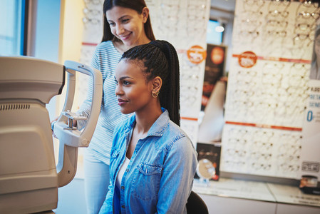 Serious black woman takes eye exam in optical shop