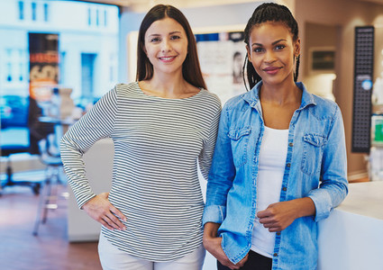 Two young happy female friends in store