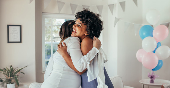 Pregnant woman hugging a friend at baby shower