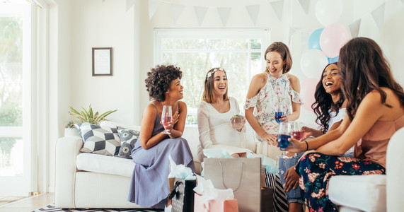 Female friends having drinks at baby shower