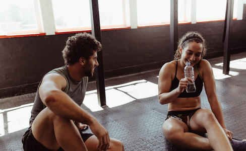 Couple relaxing after workout session at gym