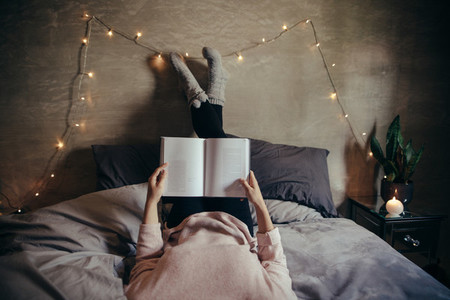 Woman lying on bed and reading book