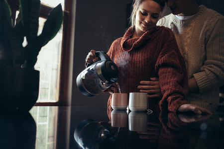 Loving young couple in kitchen making coffee