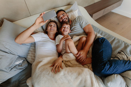 Family taking selfie on bed at home