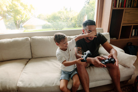 Father and son having fun playing video games at home